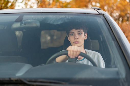 Teenage driver sitting behind the wheel of a car
